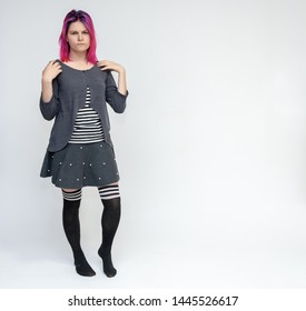 Full-length portrait of young pretty teenager girl in gray suit with beautiful purple hair on a white background in the studio. Talking, smiling, showing hands with emotions.