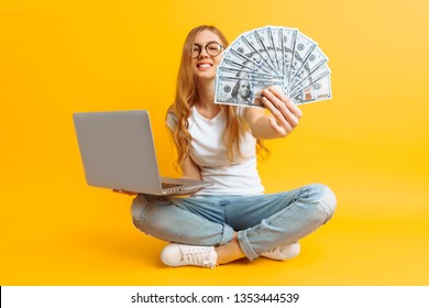 Full-length portrait of a young woman with glasses and a white T-shirt, sitting on the floor, using a portable laptop and holding money in her hand, on a yellow background