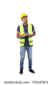 Full-length of professional Pakistani engineer wearing a denim t-shirt, light blue jeans pants, sneakers, yellow helmet and vest. He is writing on a clipboard, isolated on white background.