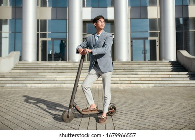 Full-length shot of asian businessman in casual suit and glasses looking aside while standing with electro scooter near office building. Modern and ecological transportation concept. Horizontal shot