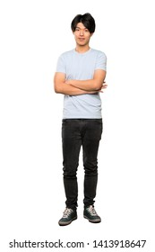 A full-length shot of a Asian man with blue shirt keeping the arms crossed in frontal position over isolated white background