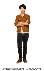 A full-length shot of a Asian man with brown jacket keeping the arms crossed in frontal position over isolated white background