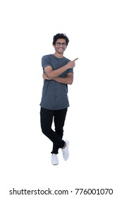 Full-length shot of attractive cheerful guy with folded arm pointing to the side. He is wearing eyeglasses,  gray t-shirt, black trousers, and white sneakers. Isolated on white background.
