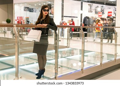Full-length shot of attractive woman dressed in jacket, skirt and heeled boots standing with white bag on balcony of shopping centre. Lady in glasses leaning against the transparent gallery in mall