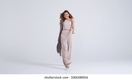 Full-length shot of beautiful girl in top and trousers walking towards camera