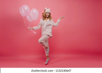 Full-length shot of birthday girl in gray socks posing in studio. Portrait of smiling young lady in silk pyjamas jumping with pink balloons.