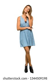 A full-length shot of a Blonde woman with jean dress having doubts and thinking over isolated white background