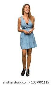 A full-length shot of a Blonde woman with jean dress keeping the arms crossed in frontal position over isolated white background