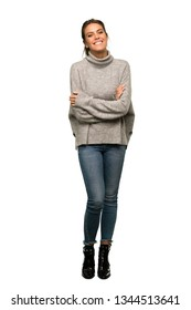 A full-length shot of a Blonde woman with turtleneck keeping the arms crossed in frontal position over isolated white background