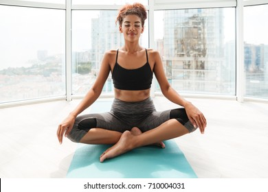 Full-length shot of calm african woman making yoga exercise at home. Sitting on floor