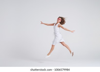 Full-length shot of cheerful girl jumping in air over white background