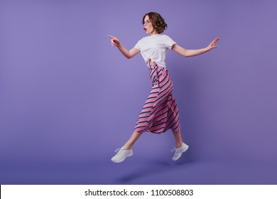 Full-length shot of excited pretty girl with wavy hairstyle jumping on purple background. Stylish good-humoured woman in sneakers having fun during photoshoot.