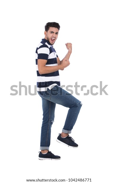 A full-length shot of an excited young man fisted up and raising a leg in a side view shot fisted up as he dancing, isolated on a white background.