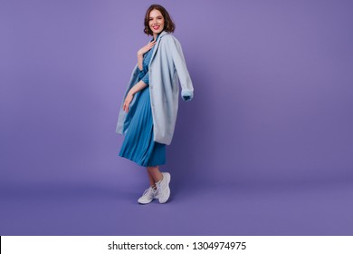 Full-length shot of fashionable girl in white sneakers wears blue coat. Indoor portrait of carefree pretty lady with curly hair.