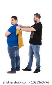 A full-length shot of a friend fits a yellow t-shirt to his friend's back, isolated on a white background.