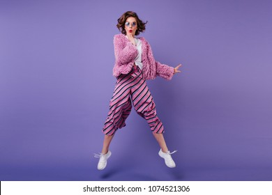 Full-length shot of glad curly woman in striped pants jumping on purple background. Indoor portrait of wonderful girl in sunglasses fooling around in studio.