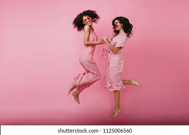 Full-length shot of graceful ladies expressing blissful emotions. Indoor portrait of pretty african girl jumping on pink background with happy face expression.