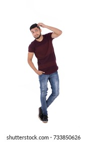 Full-length shot of handsome happy beard young man with hand in pocket smiling and looking up, guy wearing burgundy t-shirt and jeans, isolated on white background