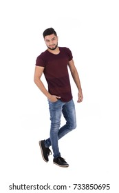 Full-length shot of handsome happy beard young man with hand in pocket smiling and looking to you, guy wearing burgundy t-shirt and jeans, isolated on white background