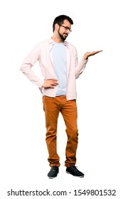 Full-length shot of Handsome man with beard holding copyspace with doubts over isolated white background
