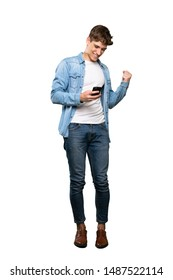 A full-length shot of a Handsome young man with phone in victory position over isolated white background