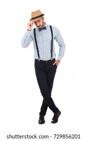 Full-length shot of handsome young man holding his hat, guy wearing light blue shirt and black pants with a violet papion, isolated on white background