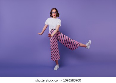 Full-length shot of jocund stylish lady in pink pants. Funny young woman with short curly hairstyle fooling around on purple background.