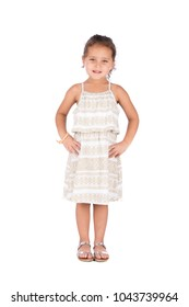 A full-length shot of a little girl wearing a beautiful dress standing hands at the waist, isolated on white background.