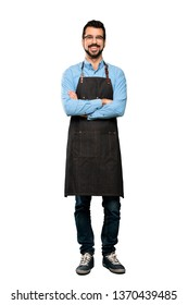 Full-length shot of Man with apron keeping the arms crossed in frontal position over isolated white background