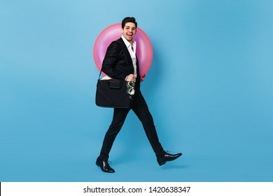 Full-length shot of man in black suit and white shirt on blue background. Brunette guy with smile poses holding inflatable circle