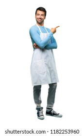 A full-length shot of a Man wearing an apron pointing to the side with a finger to present a product or an idea while looking forward smiling on isolated background