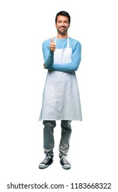 A full-length shot of a Man wearing an apron giving a thumbs up gesture and smiling because something good has happened on isolated background