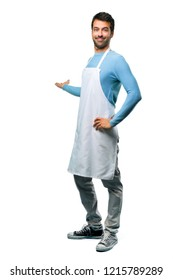 A full-length shot of a Man wearing an apron pointing back with the index finger presenting a product on isolated background