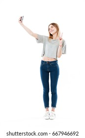 Full-length shot of positive woman making selfie on smartphone and showing peace gesture isolated over white