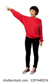 A full-length shot of a Short hair girl with red sweater pointing away over isolated white background