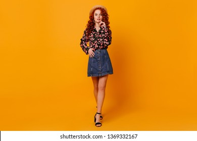 Full-length shot of slim young woman in stylish denim skirt, shirt with flower picks and hat in orange studio