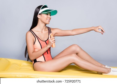 Full-length shot of smiling asian woman in coral swimsuit and visor, sitting on a pool mattress, applying a sunscreen lotion from the bottle