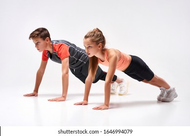 Full-length shot of teenage boy and girl engaged in sport, looking away while doing push-ups. Isolated on white background. Training, active lifestyle, team concept. Horizontal shot