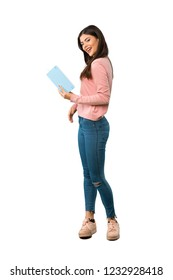 A full-length shot of a Teenager girl with pink shirt holding a book and enjoying reading