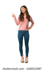 A full-length shot of a Teenager girl with pink shirt pointing finger to the side and presenting a product