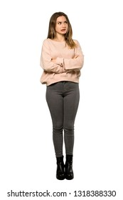 A full-length shot of a Teenager girl with pink sweater with confuse face expression while bites lip over isolated white background