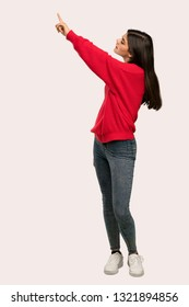 A full-length shot of a Teenager girl with red sweater pointing away over isolated background
