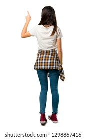 A full-length shot of a Teenager girl with shirt tied to the waist pointing back with the index finger