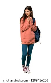A full-length shot of a Teenager girl with sweatshirt and backpack scheming something