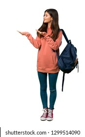 A full-length shot of a Teenager girl with sweatshirt and backpack extending hands to the side for inviting to come