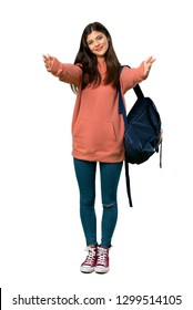 A full-length shot of a Teenager girl with sweatshirt and backpack presenting and inviting to come with hand