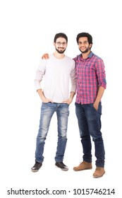 A full-length shot of two friends standing hands in pocket, one of them his hand on his friend's shoulder, isolated on a white background.