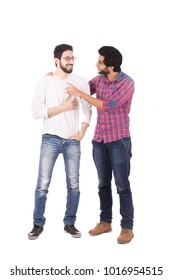 A full-length shot of two friends standing talking and joking together, smiling, isolated on a white background.