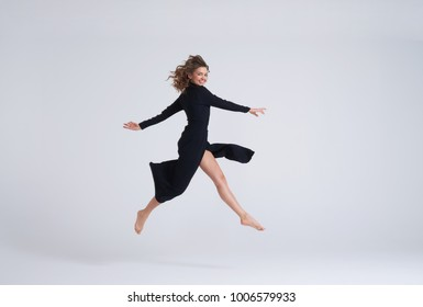 Full-length shot of young attractive woman in black dress jumping in the air