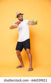Full-length shot of young bearded serious man in sunglasses aiming with water gun isolated